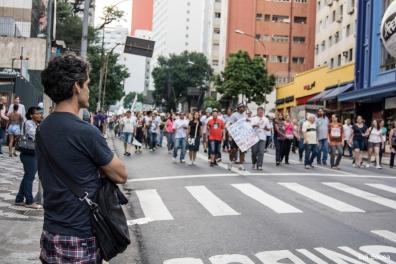Homem obeserva o protestos dos professores.