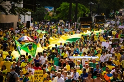 Uma multidão de pessoas carregam uma longa bandeira verde e amares na Avenida Paulista