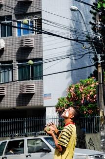 Jovem jogando bolas e fazendo malabarismo em um farol em Recife