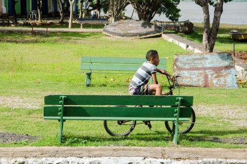 Garato sentado na bike no banco em umas das praças da cidade de Alcântara MA observando algo